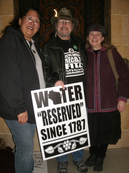Tribal members and citizens throughout Wisconsin joined forces to oppose fast-track mining legislation introduced in the Wisconsin Legislature in late 2011. The proposed bill gutted environmental protections and ignored Native American treaty rights. Pictured here (left to right) are Sherrole Benton (Green Bay, WI), Bill Krupinski (Jefferson, WI) and Laura Gauger (Duluth, MN). Recognition of tribes as sovereign nations was written into our (USA) constitution in 1787, so that is why the logo on the sign pictured here refers to that date (State Capitol, Madison, WI, January 25, 2012).